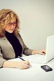 La empresaria está trabajando con el ordenador portátil fotografía de archivo