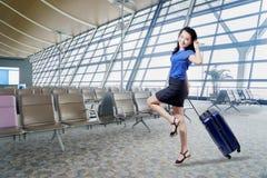 La empresaria feliz se coloca en el terminal de aeropuerto imagen de archivo libre de regalías