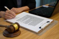 la empresaria firma el contrato abogado con el documento en el bufete de abogados fotos de archivo