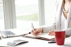 La empresaria hace una nota en cuaderno. Imágenes de archivo libres de regalías
