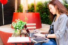 La empresaria hermosa atractiva está trabajando en el ordenador portátil en la cafetería fotos de archivo libres de regalías