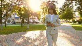 La empresaria hermosa camina a lo largo del callejón en parque con la tableta en sus manos, muchacha en un traje de negocios lige almacen de metraje de vídeo