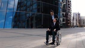 La empresaria hermosa cuida para su colega en silla de ruedas almacen de metraje de vídeo