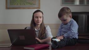 La empresaria hermosa de la madre del retrato que trabaja en la tabla de la oficina con el ordenador portátil y el bebé adorable  almacen de metraje de vídeo
