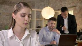 La empresaria hermosa joven está escuchando cómo sus colegas de los hombres en fondo cotillean sobre herm, concepto del sexismo almacen de metraje de vídeo