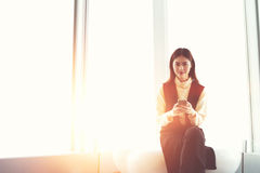 La empresaria japonesa encantadora joven con el teléfono móvil en manos está mirando la cámara Fotos de archivo libres de regalías