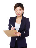 La empresaria joven asiática toma la nota sobre el tablero foto de archivo libre de regalías