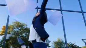 La empresaria joven celebra éxito y los papeles y los documentos que lanzan en el aire en fondo moderno del edificio de oficinas almacen de video
