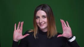 La empresaria joven con gestos del pelo de la castaña cruzó los fingeres firma la rogación para el éxito en fondo verde almacen de video