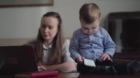 La empresaria joven de la madre que trabaja en la tabla de la oficina con el ordenador port?til y el beb? adorable se sientan en  almacen de metraje de vídeo