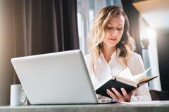 La empresaria joven en camisa es se sienta en oficina en la tabla delante del ordenador y lee notas en cuaderno foto de archivo