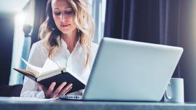 La empresaria joven en camisa es se sienta en oficina en la tabla delante del ordenador y lee notas en cuaderno estudiante fotos de archivo