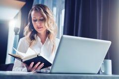 La empresaria joven en camisa es se sienta en oficina en la tabla delante del ordenador y lee notas en cuaderno estudiante imagenes de archivo