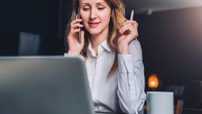 La empresaria joven en camisa se está sentando en oficina en la tabla delante del ordenador, hablando en el teléfono celular fotografía de archivo
