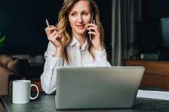 La empresaria joven en camisa se está sentando en oficina en la tabla delante del ordenador, hablando en el teléfono celular foto de archivo