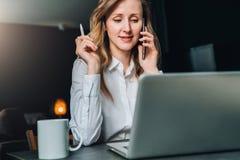 La empresaria joven en camisa se está sentando en oficina en la tabla delante del ordenador, hablando en el teléfono celular fotos de archivo libres de regalías