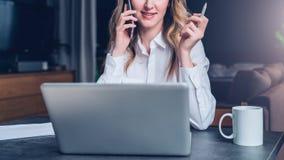 La empresaria joven en camisa se está sentando en oficina en la tabla delante del ordenador, hablando en el teléfono celular imagen de archivo