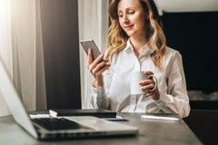 La empresaria joven en camisa se está sentando en oficina en la tabla delante del ordenador, usando smartphone, las miradas en la fotografía de archivo libre de regalías