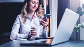 La empresaria joven en camisa se está sentando en oficina en la tabla delante del ordenador, usando smartphone, las miradas en la fotografía de archivo