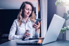 La empresaria joven en camisa se está sentando en oficina en la tabla delante del ordenador, usando smartphone, las miradas en la foto de archivo libre de regalías