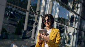 La empresaria joven en un traje está trabajando en la tableta cerca de centro de negocio de cristal moderno durante una hora de l metrajes