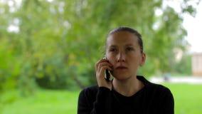 La empresaria joven escucha su interlocutor durante una conversación telefónica almacen de video