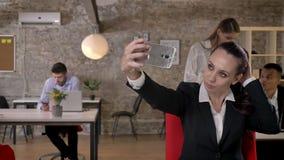 La empresaria joven está haciendo el selfie en smartphone en oficina, sus colegas es establecimiento de una red con las tecnologí metrajes