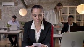 La empresaria joven está leyendo y el mensaje que mecanografía en smartphone en la oficina, sonriendo, sus colegas es establecimi almacen de video