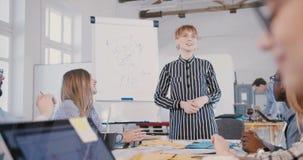 La empresaria joven feliz hermosa sonríe explicando diagramas en flipchart de los datos en la reunión multiétnica del equipo d metrajes