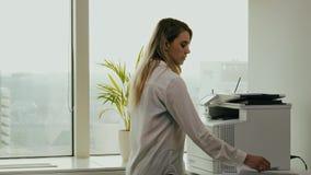 La empresaria joven imprime en la impresora en la oficina almacen de video
