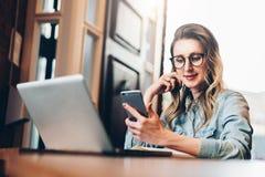 La empresaria joven se está sentando en cafetería en la tabla delante del ordenador y del cuaderno, usando smartphone Media socia fotografía de archivo