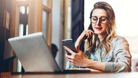 La empresaria joven se está sentando en cafetería en la tabla delante del ordenador y del cuaderno, usando smartphone Media socia fotos de archivo libres de regalías