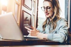 La empresaria joven se está sentando en cafetería en la tabla delante del ordenador y del cuaderno, usando smartphone Media socia foto de archivo libre de regalías