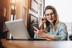 La empresaria joven se está sentando en cafetería en la tabla delante del ordenador y del cuaderno, usando smartphone Media socia fotografía de archivo libre de regalías