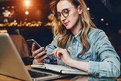 La empresaria joven se está sentando en cafetería en la tabla delante del ordenador y del cuaderno, usando smartphone Media socia fotos de archivo