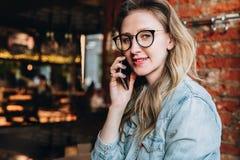La empresaria joven tiene conversaciones telefónicas Blogger alegre de la muchacha en los vidrios de moda que se sientan en el ca imagen de archivo