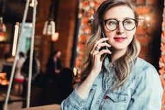 La empresaria joven tiene conversaciones telefónicas Blogger alegre de la muchacha en los vidrios de moda que se sientan en el ca imagen de archivo libre de regalías