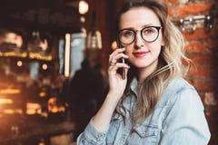 La empresaria joven tiene conversaciones telefónicas Blogger alegre de la muchacha en los vidrios de moda que se sientan en el ca foto de archivo