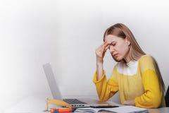 La empresaria joven tiene dolor de cabeza durante trabajo Muchacha con la computadora portátil imagenes de archivo