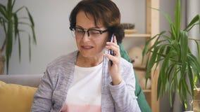 La empresaria madura encantadora está utilizando el smartphone, haciendo la llamada móvil en el interior casero almacen de video