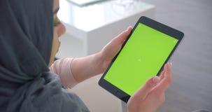 La empresaria musulm?n en hijab gira el app en la tableta con la pantalla y los relojes verdes de la croma atento almacen de metraje de vídeo