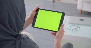 La empresaria musulmán en hijab gira el app en la tableta horizontal con la pantalla y los relojes verdes de la croma atento metrajes