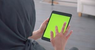 La empresaria musulmán en hijab mira atento en la tableta con la pantalla verde de la croma que se sienta en oficina metrajes