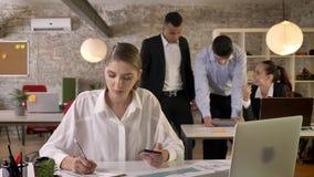 La empresaria ocupada joven está trabajando en la oficina, anotando, sosteniendo smartphone disponible, discusión en fondo almacen de video