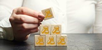 La empresaria pone o quita bloques de madera con las monedas El concepto de acumular beneficios Conceptual financiero Image Asunt imágenes de archivo libres de regalías