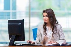 La empresaria que se sienta en el escritorio de oficina fotos de archivo