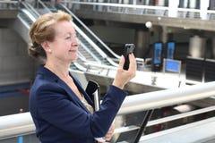 La empresaria que sostiene el teléfono elegante móvil con conecta wifi en la estación del aeropuerto o del tren, del subterráneo  imagen de archivo libre de regalías