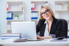 La empresaria que trabaja en el ordenador portátil en el escritorio en la oficina fotos de archivo