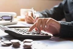 la empresaria que usa la calculadora para calcula la contabilidad de las finanzas imagen de archivo