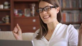 La empresaria que usaba el ordenador portátil en casa, hembra profesional que recibía buenas noticias excitó la sonrisa alegre almacen de metraje de vídeo